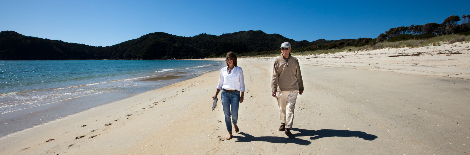 Couple walking on the beach at Awaroa - Abel Tasman NP, NZ.