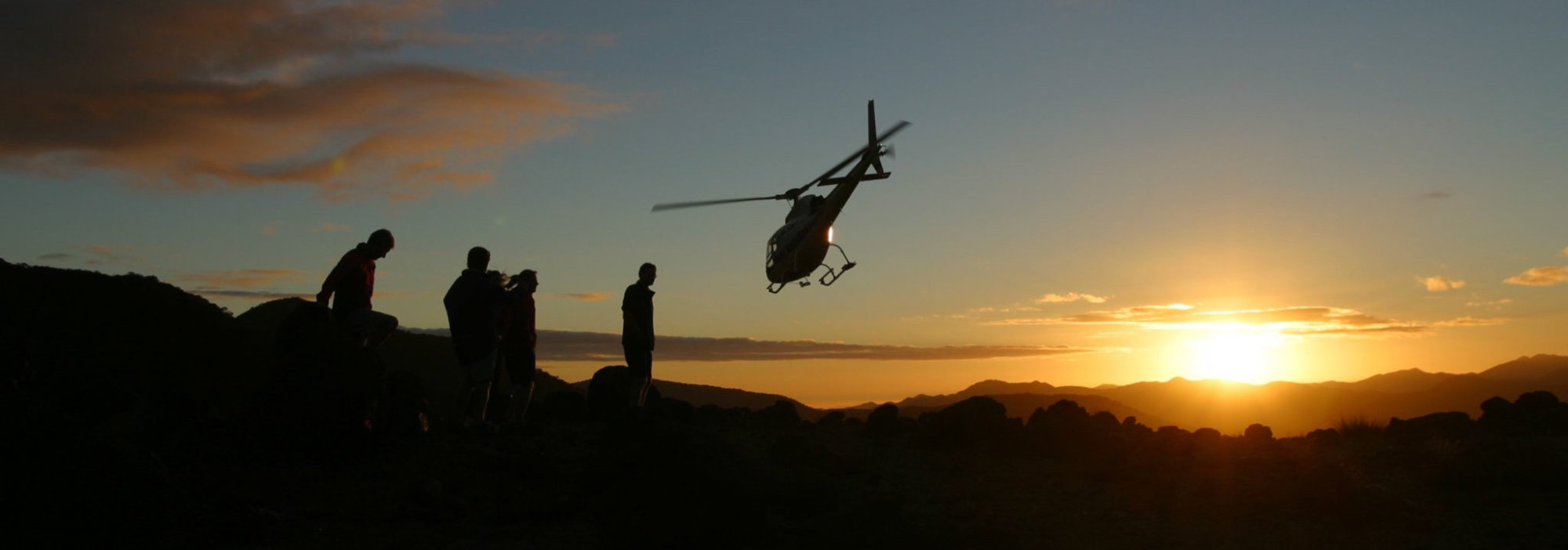 helicopter taking off into sunset
